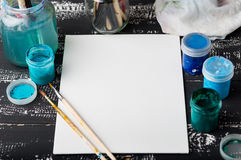 Artist`s workshop. Canvas, paint, brushes, palette knife lying on the table.Art tools.Artist workplace background.Acrylic paint an. D brushes.Art picture with royalty free stock photography