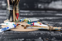 Artist`s workshop.Items for children`s creativity on a wooden background. Acrylic paint and brushes on white wooden background. Pi. Cture with copy space and for Stock Image
