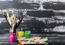 Artist`s workshop.Items for children`s creativity on a wooden background. Acrylic paint and brushes on white wooden background. Pi