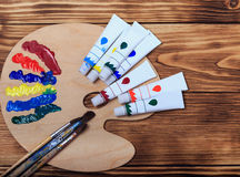 Artist`s workshop.Items for children`s creativity on a wooden background. Acrylic paint and brushes on white wooden background. Pi. Cture with copy space and for Stock Photos