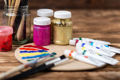 Artist`s workshop.Items for children`s creativity on a wooden background. Acrylic paint and brushes on white wooden background. Pi. Cture with copy space and for Royalty Free Stock Image