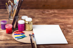 Artist`s workshop.Items for children`s creativity on a wooden background. Acrylic paint and brushes on white wooden background. Pi. Cture with copy space and for Stock Photo