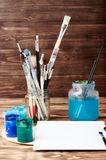 Artist`s workshop. Top view of paintbrushes palette and acrylic paints with white canvas. Set of brushes and oil paints. Art pictu Stock Photos
