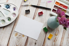 Artist s workspace with a bouquet of roses in a vase, watercolor, pen, brush, white paper on a wooden background. Royalty Free Stock Images