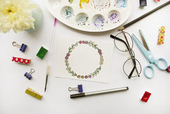 Artist`s workspace. Flat lay. Artist`s workspace. Floral wreath frame painted with watercolor, chrysanthemum, glasses, paintbrush, scissors, watercolor, palette Stock Photography