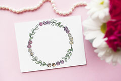 Artist`s workspace. Floral wreath frame painted with watercolor, vase with a bouquet of flowers, bead. Flat lay.  Stock Photo