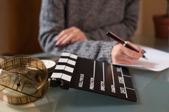 Artist screenwriter desktop detail clapper board. Artist screenwriter desktop detail with movie clapper board and filmstrip with woman`s hand working in Stock Images