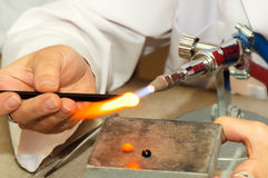 Artist shaping glass. Artist shaping hot glass using a gas flame Stock Photos