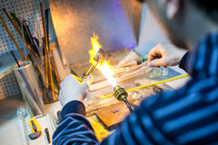 Artist shaping hot glass into a figurine with gas Stock Photos