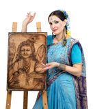 Artist showing pyrography painting Prosperity on the easel. Woman artist in Indian sari showing pyrography painting Prosperity on the easel royalty free stock photography