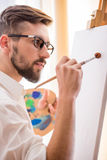 Artist. Side view of young artist  with brush and palette is going to painting a picture Royalty Free Stock Photos