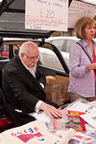 Artist Sir Peter Blake at the 2010 Art Car Boot Fa. Famous artist Sir Peter Blake sits in the boot of his car, reaching for his work at the 2010 Art Car Boot Stock Photography