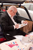 Artist Sir Peter Blake at the 2010 Art Car Boot Fa. Famous artist Sir Peter Blake sitting on the back of his car, signing one of his prints at the 2010 Art car Stock Photo
