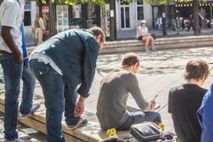 Artist sketches with onlookers in a Paris square Royalty Free Stock Photos