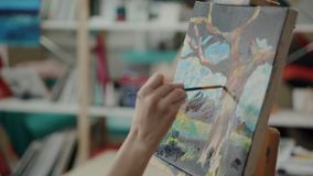 Woman is depicting landscape on canvas by acrylic paints in studio. Artist is sketching a picture in workshop. Close-up of hand holding brush and making strokes stock video