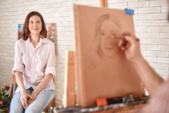 Artist Sketching Portrait of Beautiful Smiling Model. Portrait of artist drawing  portrait of beautiful young women sitting in front of him in art studio, focus Stock Image