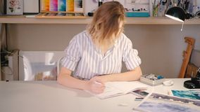 Artist woman desk sketching home art studio. Artist sketching. Young blonde woman sitting at desk drawing in sketchpad. Model on smartphone screen. Home art stock video