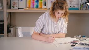 Artist woman desk sketching home art studio. Artist sketching. Young blonde woman sitting at desk drawing in sketchpad. Model on smartphone screen. Home art stock video footage