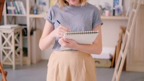 Artist sketching young female standing drawing. Tracking shot of artist sketching. Young female sketchbook in hands standing drawing. Inspiration imagination stock footage