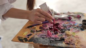 Artist squeezes the paint from the tube on palette. The artist squeezes the paint from the tube on the palette, close-up. The artist`s hands close-up on the stock video