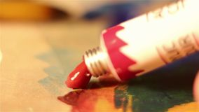 The artist squeezes the red paint from the tube onto the palette. Macro shooting stock footage