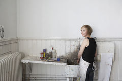 Artist Standing By Dirty Sink In Studio. Rear view of a smiling female artist standing by dirty sink in studio royalty free stock photography