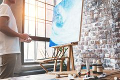Artist stands in front of the easel with a canvas and considers his work. Painter in art studio. Hobby and creative occupation con. Cept. Lens flare effect royalty free stock photography