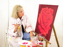 Artist Studies Her Painting of a Rose Royalty Free Stock Photography