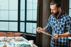 Artist studio artwork man contemplation reflection. Artist studio. Man creating artwork. Board with painting in hands. Serious facial expression. Contemplation royalty free stock photo