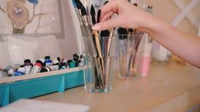 Artist supplies hand choosing paintbrushes studio. Artist supplies closeup. Woman hand choosing paintbrushes. Neatly organized art studio workplace. Art hobby stock video footage