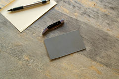 Artist supplies on old table. A pencil, paper, knife and grey card are seen on an old wooden table Stock Photo