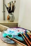 Artist& x27; taller de s Caballete con los cepillos y los tubos de la pintura Fotografía de archivo libre de regalías