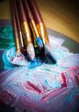 Artist& x27; taller de s Caballete con los cepillos y los tubos de la pintura Imagen de archivo libre de regalías