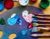 Artist& x27; taller de s Caballete con los cepillos y los tubos de la pintura Imagen de archivo