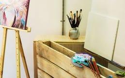 Artist& x27; taller de s Caballete con los cepillos y los tubos de la pintura Fotografía de archivo