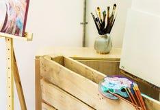 Artist& x27; taller de s Caballete con los cepillos y los tubos de la pintura Fotos de archivo libres de regalías