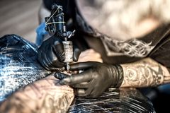 Artist at tattoo shop drawing with ink on skin Stock Photography