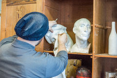 Artist/teacher cleaning sculptures with a piece of cloth Stock Photography