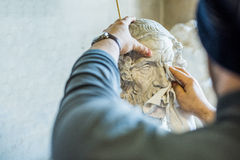 Artist/teacher cleaning sculptures for study with a piece of cloth - close up view Royalty Free Stock Photos