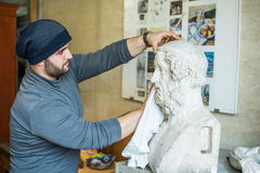 Artist/teacher cleaning sculptures for study with a piece of cloth - side view Stock Images