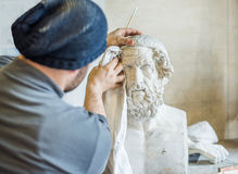 Artist/teacher cleaning sculptures for study with a piece of cloth Stock Images
