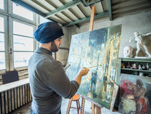 Artist/teacher painting an artwork for a contest in his studio Royalty Free Stock Photos