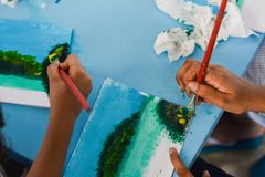 Artist teaching his student how to paint beautiful tropical landscape during painting lesson royalty free stock images