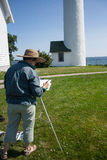 Artist at Tibbetts Point Lighthouse. An senior artist, using watercolors, is at work on a depiction of the Tibbetts Point Lighthouse at Cape Vincent, New York stock photos