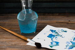 Artist tools, paper with blue paint. On wooden background Royalty Free Stock Photo