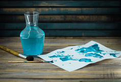 Artist tools, paper with blue paint. On wooden background Royalty Free Stock Photos