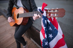 Artist with the US flag playing the guitar. Acoustic concert on the roof. Unrecognizable teenager on vacation at a party on Independence Day Stock Photography