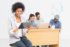 Artist using digital tablet with colleagues in background at office Stock Photography