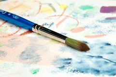 Artist Watercolor Brush. A blue watercolor brush with a green and brown tip lays on top of a color piece of paper Royalty Free Stock Photos