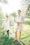 Artist with watercolor painting of bride in wedding dress outdoo Stock Photos